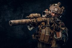 Elite unit, special forces soldier in camouflage uniform holding an assault rifle with a laser sight and aims at the. Close-up studio photo. Elite unit, special stock photo