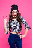 Close up studio portrait of cheerful blonde hipster girl going crazy making funny face and showing her tongue. Pink wall Royalty Free Stock Images