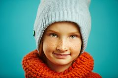 Close up studio portrait of child girl wearing a round scarf orange and blue winter hat. Seasonal assortment of children royalty free stock photography