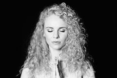 Portrait of a pretty curly blonde woman, holding hands together, eyes closed. Close up studio portrait of a pretty curly blonde woman, holding hands together royalty free stock images