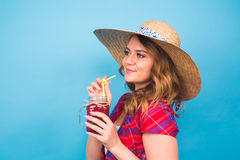 Close up studio portrait of sexy woman wearing bright outfit holding and drinking tasty green smoothie milkshake. Over Stock Image
