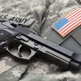 Close up studio shot of a handgun over USA solder's uniform with shoulder patch on it Royalty Free Stock Photos