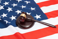 Close up studio shot of a judge gavel and soundboard laying over USA flag Stock Photography
