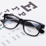 Close up studio shot of a table for eyesight test with neat glasses over it. Close up shot of a table for eyesight test with neat glasses over it Royalty Free Stock Photos
