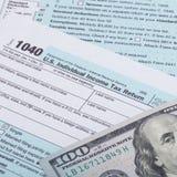 Close up studio shot of US 1040 Tax Form and dollars Royalty Free Stock Photos