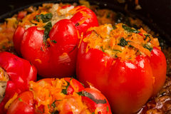 Close-up of stuffed red sweet pepper. Close-up of red sweet peppers, stuffed with rice and vegetables, in a frying pan Stock Images
