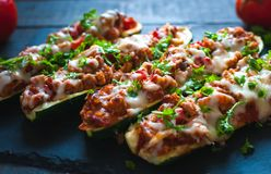 Close-up of stuffed zucchini boats with ground beef, spicy tomato sauce, cheese and fresh parsley, on dark background. Close-up of homemade stuffed zucchini royalty free stock photography