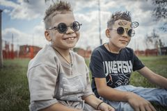 Close up of boys sitting in the park on green grass. Happy family concept. royalty free stock photo