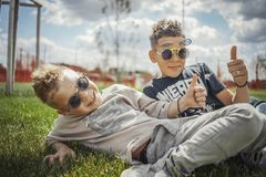 Close up of boys sitting in the park on green grass. Happy family concept. royalty free stock image
