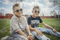 Close up of boys sitting in the park on green grass. Happy family concept. stock image