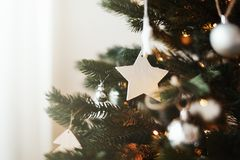 Close up of stylish Christmas tree toys and garland lights on branches. royalty free stock image