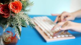 Close-up. stylish greeting video card. female hands are typing on a pink keyboard, next to a flower. on a blue stock photos