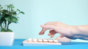 Close-up. stylish greeting video card. female hands are typing on a pink keyboard, next to a flower. on a blue royalty free stock photo