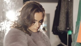 Close up of stylish lady choosing the coat in boutique stock video footage