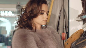 Close up of stylish lady choosing the fur coat in boutique stock video footage