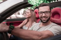 Close up.stylish man with his girlfriend traveling in a convertible car. royalty free stock image