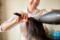 Close up of stylist making hairdo at salon Stock Photo