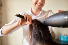 Close up of stylist making hairdo at salon Stock Photo