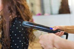 Close up of stylist's hand using curling iron for hair curls. Royalty Free Stock Photos