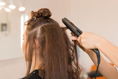 Close up of stylist's hand using curling iron for hair curls. Stock Images