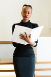Close-up of successful African or black American business woman holding and looking at big white file Stock Image