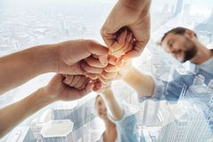 Close up of successful team with fists together. Professional workers. Close up of successful colleagues keeping fists together while standing in circle and Stock Photography