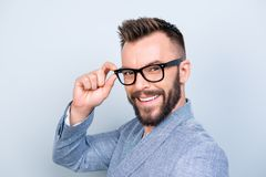 Close up of successful young handsome brunet bearded businessman. In formal outfit and black glasses on pure background. So cheerful and stylish, attractive and Royalty Free Stock Photos