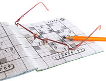 Close up of sudoku game, glasses and yellow pencil Royalty Free Stock Photos