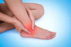 Close up suffering male pain in ankle on blue background. Stock Photos