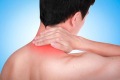 Close up suffering male pain in neck on blue background. Stock Image