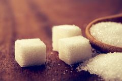 Close up a sugar cubes and cane in wooden spoon on the table ,re Royalty Free Stock Photography