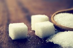 Close up a sugar cubes and cane in wooden spoon on the table ,re Royalty Free Stock Photo
