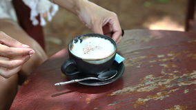 Close up sugar pouring into cup of coffee stock footage