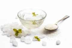 Close up of sugar syrup in a glass bowl along with sugar cubes and some mentha or mint leaves. Cube sugar or crystallized sugar with its syrup and mint leaves stock photo