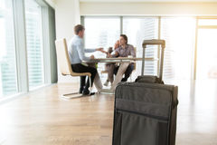 Close up of a suitcase in a flat. Close up of suitcase in real estate agency, young couple got help with mortgage interest, signed contract for a long-term royalty free stock photography
