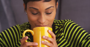 Close up of sultry black woman smiling with mug Stock Photography