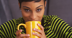 Close up of sultry black woman smiling with mug Royalty Free Stock Photo
