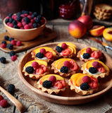 Close up. Summer delicious dessert with various fruits. Fresh berry tartlet or cake with vanilla custard, raspberry Stock Images