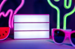 Close up Summer light box flamingo, cactus, sunglasses and blank light box with neon pink and blue light on table with monstera royalty free stock photos