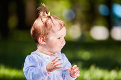 Close-up summer portrait of beautiful baby girl on the lawn in the park. Cute little girl in the white dress. Summer or spring season in the city park. Warm Royalty Free Stock Photography