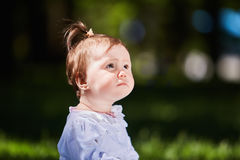 Close-up summer portrait of beautiful baby girl on the lawn in the park. Cute little girl in the white dress. Summer or spring season in the city park. Warm Royalty Free Stock Images