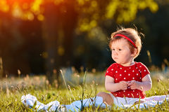 Close-up summer portrait of beautiful baby girl on the lawn in the park. Cute little girl in the white dress. Summer or spring season in the city park. Warm Royalty Free Stock Image