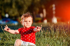 Close-up summer portrait of beautiful baby girl on the lawn in the park. Cute little girl in the white dress. Summer or spring season in the city park. Warm Stock Photo
