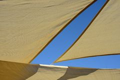 Close up of sun shade. Ivory colour with the blue sky which form geometric shapes royalty free stock images