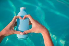 Close up of sunblock in female hands making heart Royalty Free Stock Image
