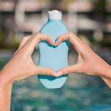 Close up of sunblock in female hands making heart. Close up of sunblock in female hands royalty free stock image
