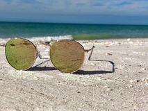 Close up of Sunglasses on a beach vacation royalty free stock photos