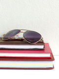 Close up sunglasses and stack of notebook Stock Photo