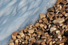 Pebble stones and foamy water on a riverbed. Close-up of sunlit brown pebble stones and bluish foamy water on a riverbed Royalty Free Stock Photo