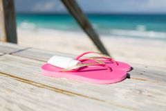 Close up of sunscreen and slippers at seaside Stock Images